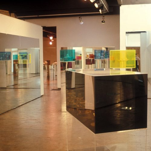 multicoloured plexiglas cubes displayed on mirrored and transparent plinths